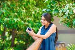 使用手机的美丽的两种人种的青少年的女孩户外由铁路 免版税库存照片