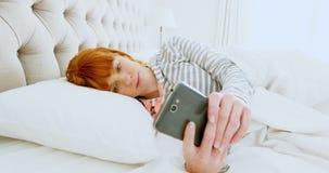 使用手机的美丽的妇女,当放松在床4k上时 影视素材