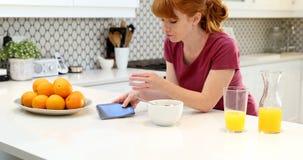 使用手机的美丽的妇女,当食用早餐4k时 股票视频