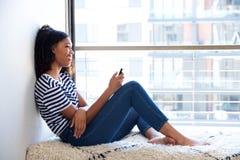 使用手机的美丽的年轻黑人妇女由窗口 库存照片