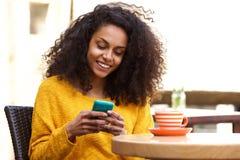 使用手机的美丽的非洲妇女在咖啡店 免版税图库摄影