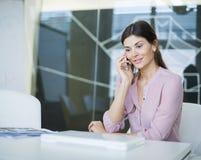 使用手机的美丽的年轻女实业家在会议桌 库存图片