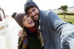 使用手机的美好的年轻夫妇在Th的一个冷的冬天 免版税库存图片
