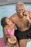 使用手机的老人坐由与孙女(5-6)画象的水池。 免版税图库摄影