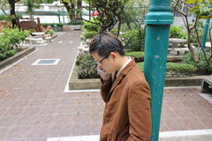 使用手机的英俊的年轻商人,当倾斜一根绿色杆在室外公园时 免版税库存照片