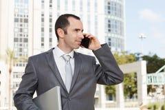 使用手机的英俊的年轻商人在现代前面 免版税库存照片