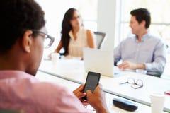 使用手机的设计师在会议期间 免版税图库摄影