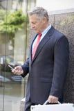 使用手机的资深商人 免版税库存图片