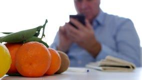 使用手机的轻松的人文本有报纸和新鲜水果的在表上 股票视频