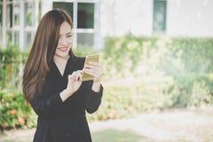 使用手机的逗人喜爱的亚裔女孩在公园 免版税库存图片