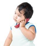 使用手机的逗人喜爱的亚裔男孩 库存图片