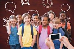 使用手机的逗人喜爱的学生的综合图象 库存图片