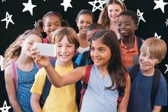 使用手机的逗人喜爱的学生的综合图象 免版税库存图片