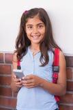 使用手机的逗人喜爱的学生 图库摄影