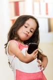使用手机的逗人喜爱的小女孩采取selfie 免版税库存图片
