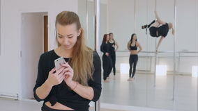 使用手机的逗人喜爱的杆舞蹈家在杆舞蹈课期间 股票视频