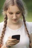使用手机的青少年的女孩 免版税图库摄影