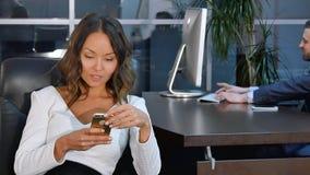 使用手机的年轻亚裔女实业家在办公室 库存照片