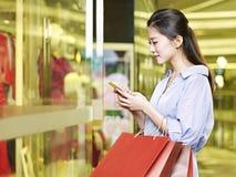 使用手机的年轻亚裔妇女,当购物时 免版税库存照片