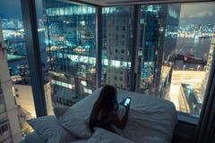 使用手机的年轻可爱的妇女在床 库存照片