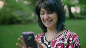 使用手机的年轻可爱的妇女在微笑和笑4k的公园 影视素材