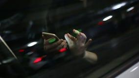 使用手机的年轻可爱的妇女在汽车在地下停车处 慢的行动 股票录像