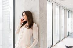 使用手机的年轻女实业家,当倾斜在墙壁在新的办公室时 免版税库存照片