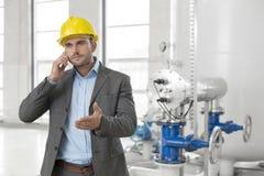 使用手机的年轻男性工程师在产业 免版税库存照片