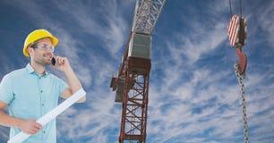 使用手机的建筑师,当拿着方案由起重机反对天空时 库存图片