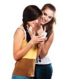 使用手机的年轻美丽的女孩送和接受sms 免版税库存图片