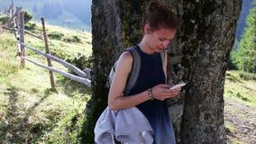 使用手机的年轻美丽的妇女在树下在山 影视素材