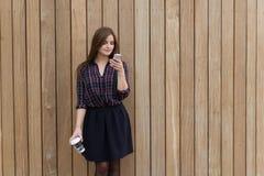 使用手机的年轻美丽的妇女,当站立与时拿走咖啡对有拷贝空间的木墙壁 免版税库存图片