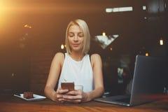 使用手机的年轻行家女孩,当享受她的业余时间在网书时的工作以后 库存照片