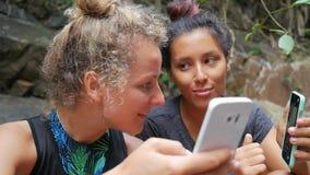 使用手机的年轻远足者女孩坐瀑布在慢动作热带的森林HD 股票视频