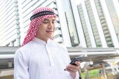 使用手机的年轻阿拉伯商人,当走在c时 免版税库存照片
