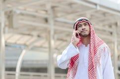 使用手机的年轻阿拉伯商人,当走在c时 库存图片