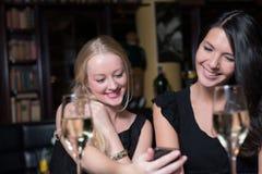 使用手机,两个妇女朋友在夜 免版税图库摄影