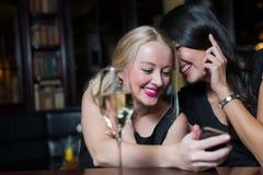 使用手机,两名妇女在夜 免版税库存图片