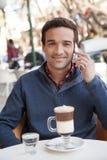 使用手机,供以人员坐在街道 免版税库存照片
