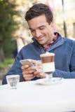 使用手机,供以人员坐在街道 库存图片