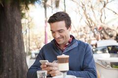 使用手机,供以人员坐在街道 免版税图库摄影