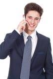 使用手机的微笑的年轻执行委员 库存图片