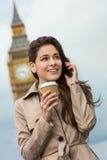 使用手机,大本钟,伦敦,英国的妇女饮用的咖啡 免版税库存图片