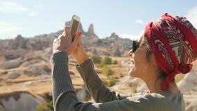 使用手机,年轻混合的族种旅游女孩为沙漠谷照相 Cappadocia,土耳其 4K 股票视频