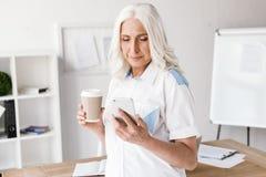 使用手机,成熟愉快的妇女饮用的咖啡 免版税库存图片