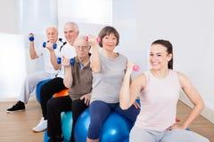 使用手重量的人们,当坐健身球时 免版税库存照片