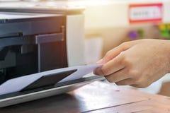 使用打印机 手对负纸在完成的打印以后 免版税库存照片