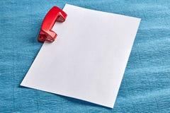 使用打孔器,猛击白皮书空白纸  库存图片