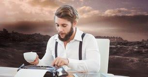 使用打字机的男性行家,当拿着咖啡杯反对海时 图库摄影