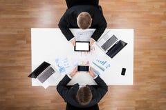 使用技术的商人与在表上的财政图 库存图片